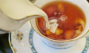 scheutje melk wordt toegevoegd aan een kopje thee
