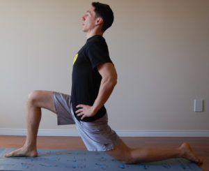 man doet kneeling warrior stretch in kamer