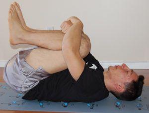 man doet knees pulled in stretch op matje