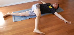 man doet star stretch positie op matje