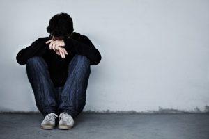 Droevige man zit gehurkt in een hoekje tegen de muur