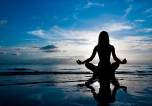 zittende vrouw doet aan meditatie bij zonsondergang