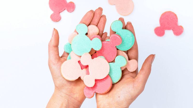 vrouw houdt kleurrijke figuur koekjes in handen vast