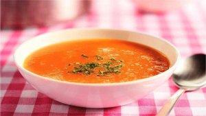 tomatensoep met lepel uitgelicht op tafel