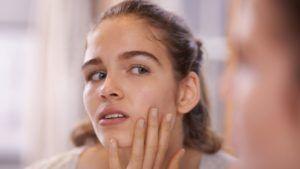 jonge vrouw kijkt in de spiegel naar puistjes op haar gezicht