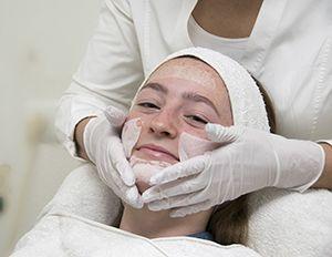 Vrouw krijgt acne behandeling door zorgverlener