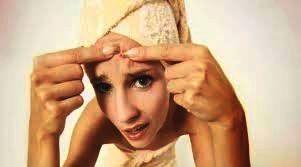 Vrouw komt uit douche en knijpt puistjes uit voor de spiegel