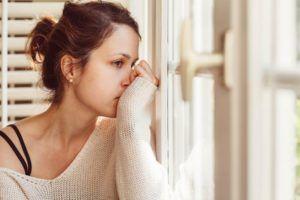 femme pensive assise à une fenêtre