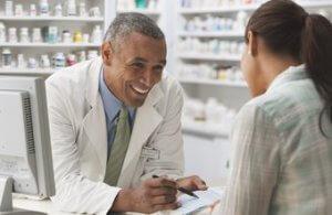 lachende apotheker praat met vrouwelijke klant