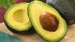 avocado open gesneden op houten plank