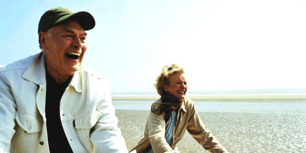 ouder echtpaar lacht en fietst op het strand op klaarlichte dag