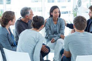 vrouw wordt in cirkel gesteund door leden van een praatgroep