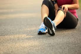 vrouw in sportkleding zit op de grond en voelt aan knie