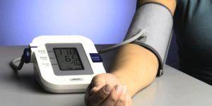 vrouw legt arm op bureau en meet haar bloeddruk