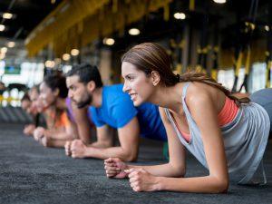 sporters doen een plankhouding op de grond