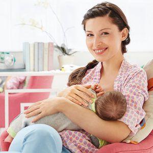 Vrouw zit op de bank en geeft borstvoeding aan baby