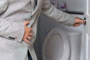 Man grijpt naar buik en maakt toiletdeur open