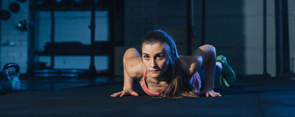 Vrouw in sportkleren doet een push-up