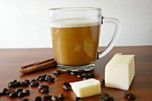 bulletproof koffie met klontje boter en koffiebonen op houten tafel