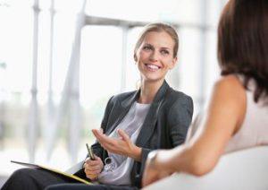 glimlachende vrouw in gesprek met een andere vrouw