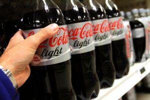 man pakt een cola light fles uit de supermarktschappen