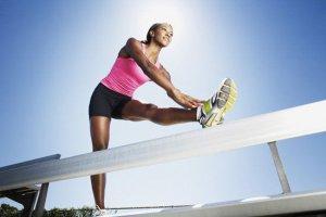 joggende vrouw rekt haar linkerbeen op een hek
