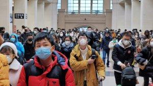 Aziaten lopen met mondkapjes rond in binnenhal