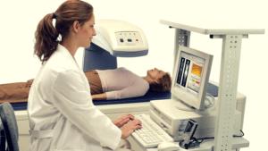 vrouwelijke patiënt ligt onder DEXA scan en wordt begeleid door arts