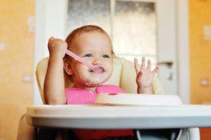Baby zittend op kinderstoel smult van havermout
