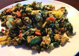 Eieren met spinazie en broccoli op wit bord