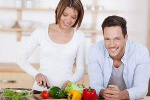 Gelukkig koppel is de groenten aan het snijden in de keuken