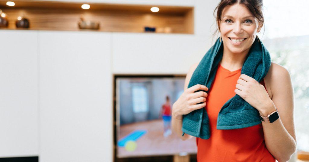 Vrouw heeft handdoek om nek en lacht naar camera