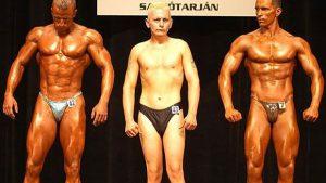 2 bodybuilders op het podium met 1 slanke man ertussen