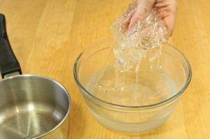 man pakt gelatine met zijn hand uit glazen kom