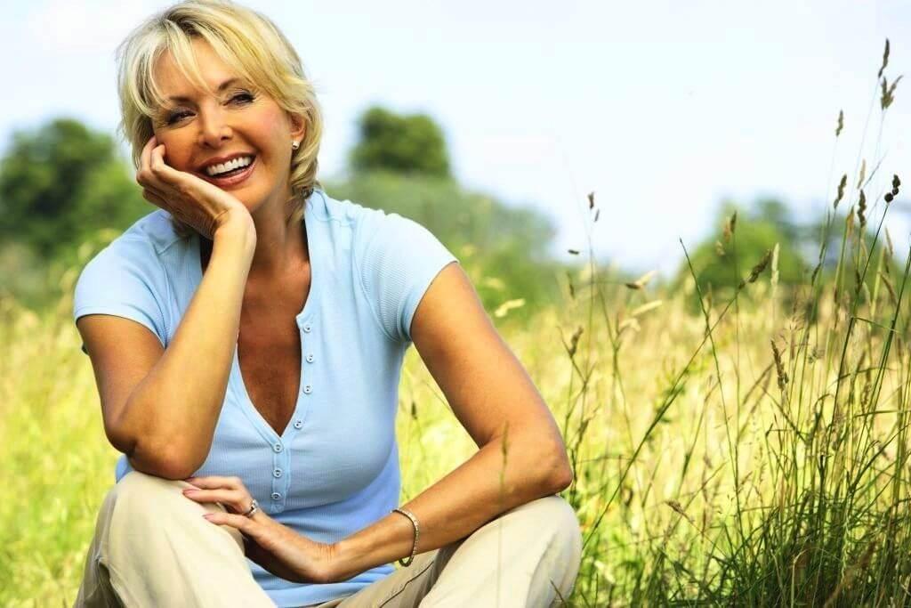 Zittende knappe oudere vrouw in de natuur trekt lachend gezicht