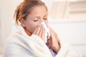 vrouw verkouden en snuit neus in doekje