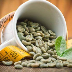 Groene koffie bonen extract uit een kopje op houten tafel
