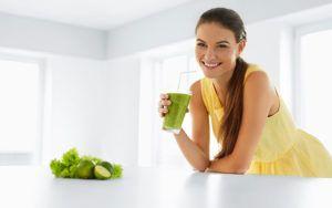 vrouw staat in keuken en geniet van haar groentesapje