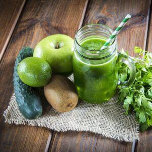 groene smoothie naast groentes op een jute zak op houten tafel