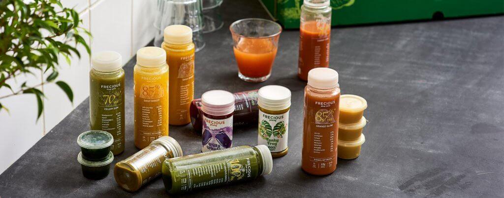 Verschillende soorten frecious sapjes in flesjes op keukentafel