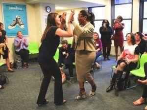 Presentatrice Opray Winfrey geeft high five aan vrouw tijdens bijeenkomst