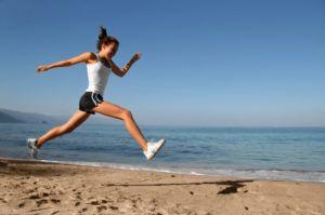 sportieve vrouw rent over het strand bij daglicht