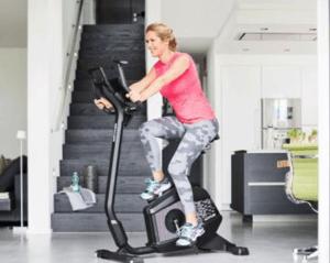 vrouw zit op hometrainer binnenshuis