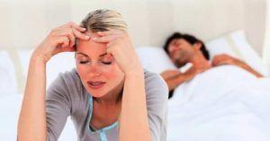 vrouw stapt uit bed omdat ze zich niet lekker voelt