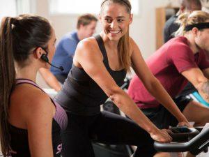 sportende vrouw op fietstrainer lacht naar sportinstructrice