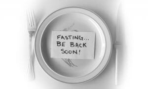 Geschreven briefje met de tekst 'vasten ben zo terug' op een maaltijdbord