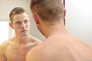 jongeman met ontbloot bovenlijf kijkt in de spiegel