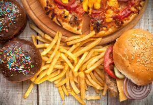 Friet, gebak, hamburger en pizza op houten tafel