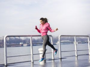 joggende vrouw maakt sprongetje op kade