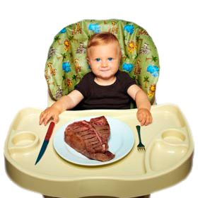 kind in kinderstoel met stuk vlees op het bord